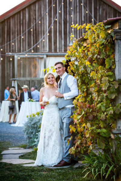 Bride and Groom in front of historic barn for wedding reception